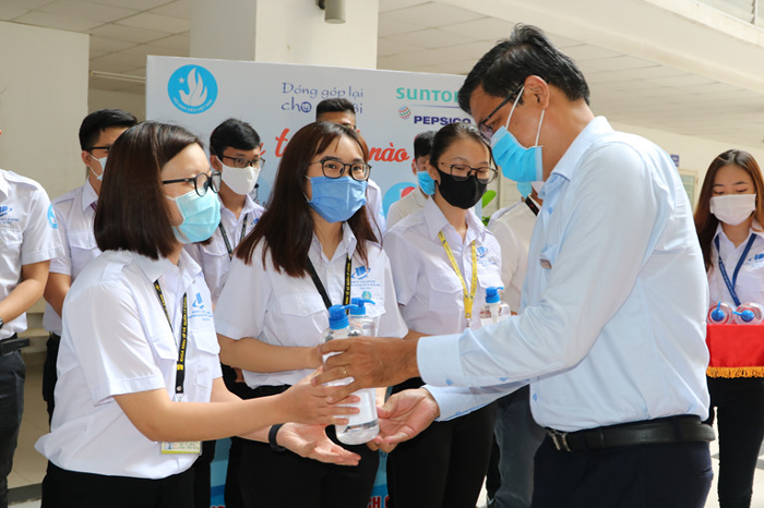 PGS. TS Nguyễn Minh Hà - Hiệu trưởng nhà trường tặng nước rửa tay cho các bạn sinh viên. Ảnh Lê Thanh, Báo Thanh niên.