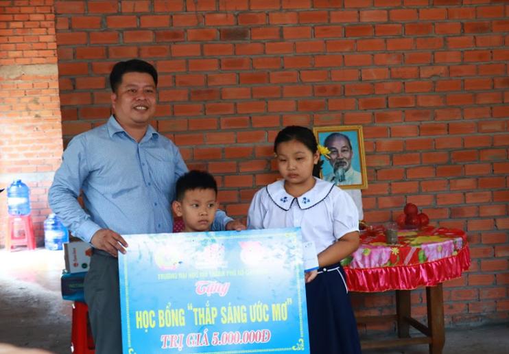 TS. Lê Nguyễn Quốc Khang – Đảng ủy viên, Phó Hiệu trưởng nhà trường trao tặng học bổng trị giá 5 triệu đồng cho 2 con của hộ gia đình